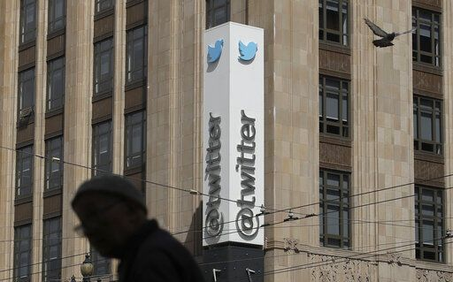 FILE - In this July 9, 2019, file photo a pedestrian walks across the street from the Twitter office building in San Francisco. A complaint unsealed in a federal court detailed a coordinated effort by Saudi officials to recruit employees at the social media giant who could tap into the Twitter accounts of political opponents and access their personal data, including internet protocol addresses that can give up a user's location.