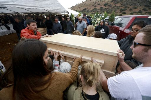 Family and friends unload the coffins that contain the remains of Rhonita Miller, and four of her young children Krystal and Howard, and twins Titus and Tiana, who were murdered by drug cartel gunmen earlier in the week, for a burial service at the cemetery in Colonia Le Baron, Mexico, Friday, Nov. 8, 2019. The bodies of Miller and four of her children were taken in a convoy of pickup trucks and SUVS, on the same dirt-and-rock mountainous road where they were killed Monday, for burial in the community of Colonia Le Baron in Chihuahua state.