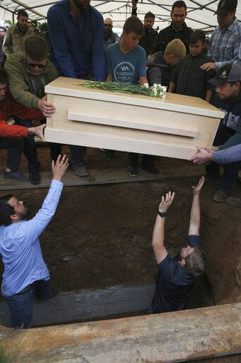 The coffin that contains the remains of 12-year-old Howard Jacob Miller Jr. is lowered into a grave at the cemetery in Colonia Le Baron, Mexico, Friday, Nov. 8, 2019, during a burial service for Rhonita Miller and four of her young children, who were murdered by drug cartel gunmen. The bodies of Miller and four of her children were taken in a convoy of pickup trucks and SUVS, on the same dirt-and-rock mountainous road where they were killed Monday, for burial in the community of Colonia Le Baron in Chihuahua state.