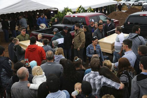 Family and friends unload the coffins that contain the remains of Rhonita Miller and four of her young children Krystal and Howard, and twins Titus and Tiana, who were murdered by drug cartel gunmen earlier in the week, for a burial service at the cemetery in Colonia Le Baron, Mexico, Friday, Nov. 8, 2019. The bodies of Miller and four of her children were taken in a convoy of pickup trucks and SUVS, on the same dirt-and-rock mountainous road where they were killed Monday, for burial in the community of Colonia Le Baron in Chihuahua state.