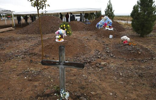 Freshly dug graves, top of photo, are prepared for Rhonita Miller, 30, and four of her young children Krystal and Howard, and twins Titus and Tiana, who were murdered by drug cartel gunmen, before their burial at a cemetery in LeBaron, Chihuahua state, Mexico, Friday, Nov. 8, 2019. A total of three women and six of their children, from the extended LeBaron family, were gunned down in a cartel ambush while traveling along Mexico's Chihuahua and Sonora state border on Monday. The graves in the foreground are not related to the burial of the Miller family.