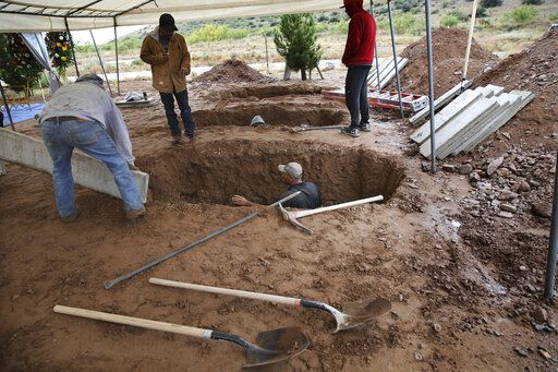 Men dig graves for Rhonita Miller, 30, and four of her young children Krystal and Howard, and twins Titus and Tiana, who were murdered by drug cartel gunmen, before their burial at a cemetery in LeBaron, Chihuahua state, Mexico, Friday, Nov. 8, 2019. A total of three women and six of their children, from the extended LeBaron family, were gunned down in a cartel ambush while traveling along Mexico's Chihuahua and Sonora state border on Monday.