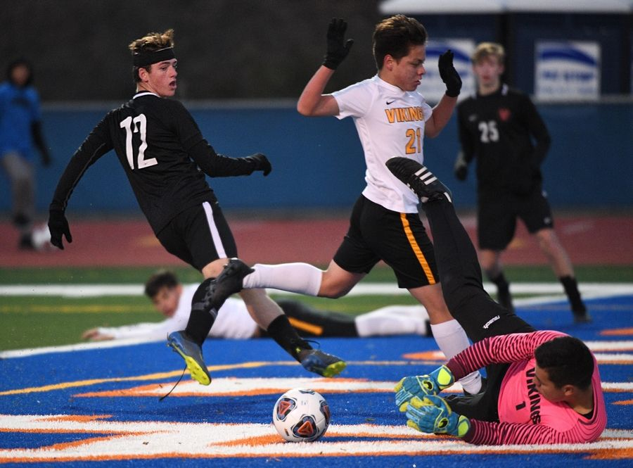 Benet Academy's Nick Renfro turns to see St. Laurence goalkeeper Fernando Cervantez stop his shot in the second half in the Class 2A boys state semifinal game in Hoffman Estates Friday.