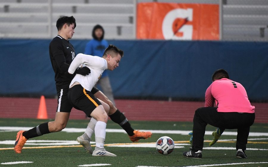 Benet Academy's Michael Fernandes is blocked from the ball by St. Laurence's Julian Cardiel and goalkeeper Fernando Cervantez picks it up in the Class 2A boys state semifinal game in Hoffman Estates Friday.