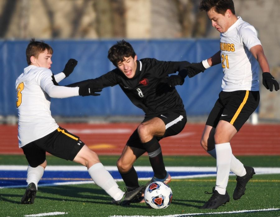 Benet Academy's Sam Hepburn plays against St. Laurence's Thomas Suchecki and Jessie Cardiel in the Class 2A boys state semifinal game in Hoffman Estates Friday.