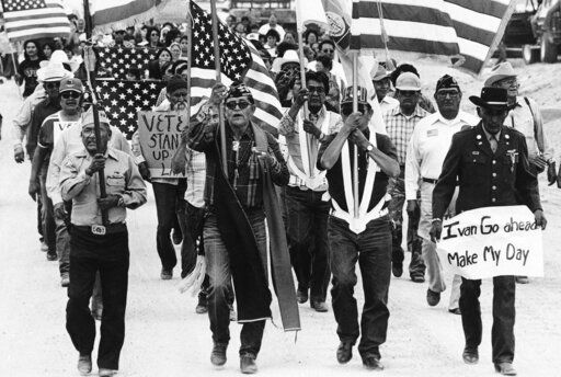 "In this July 8, 1986, file photo, World War II Navajo veterans and supporters march through the reservation in a show of solidarity against giving up any of their land to the Hopis in Arizona. ""The Warrior Tradition,"" a new film set to air on PBS stations Monday, Nov. 11, examines the history of Native Americans in the U.S. military since World War I."