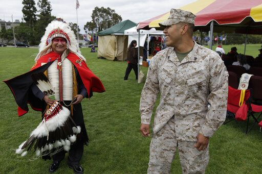 "In this June 15, 2012, file photo, Blas Preciado, left, a Vietnam War veteran of the Kiowa tribe, talks with Marine Cpl. Frank Tartsah, right, also of the Kiowa tribe, during a Native American blessing for veteran and active-duty servicemen in Camp Pendleton, Calif. ""The Warrior Tradition,"" a new film set to air on most PBS stations Monday, Nov. 11, 2019, examines the history of Native Americans in the U.S. military since World War I."
