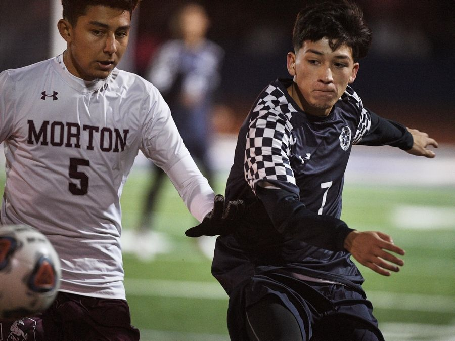 West Chicago's Diego Cortes and Morton's Juan Hernandez chase the ball in the Class 3A state soccer championship in Hoffman Estates Saturday.