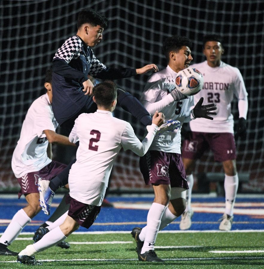 West Chicago's Moises Morfin kicks the ball out of a crowd of Morton players in the Class 3A state soccer championship in Hoffman Estates Saturday.