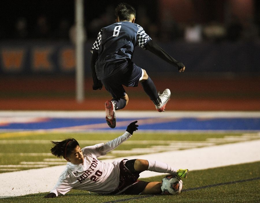 West Chicago's Moises Morfin jumps over Morton's Uriel Sotelo in the Class 3A state soccer championship in Hoffman Estates Saturday.
