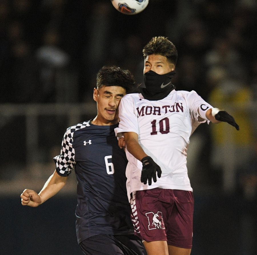 West Chicago's Tristan Alfaro and Morton's Edwin Zizumbo compete for a header in the Class 3A state soccer championship in Hoffman Estates Saturday.