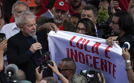 "Brazil's former President Luiz Inacio Lula da Silva holds the corner of a banner that reads in Portuguese ""Lula is innocent"" as he speaks to supporters outside the Federal Police headquarters where he was imprisoned on corruption charges in Curitiba, Brazil, Friday, Nov. 8, 2019. Da Silva walked out of the prison Friday, less than a day after the Supreme Court ruled that a person can be imprisoned only after all the appeals have been exhausted."