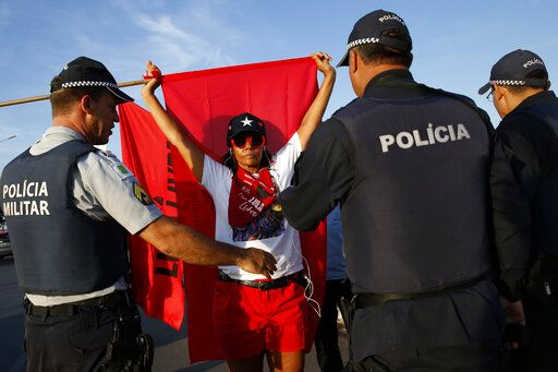 Police form a cordon between supporters of jailed former President Luiz Inacio Lula da Silva and President Jair Bolsonaro, as both groups keep vigil outside the Supreme Court in Brasilia, Brazil, Thursday, Nov. 7, 2019. Brazil's highest court reached a narrow decision that could release almost 5,000 inmates who are still appealing their convictions, including jailed former President Luiz Inácio Lula da Silva. The country's Supreme Court decided on a 6-5 vote Thursday night that a person can be imprisoned only after all appeals to higher courts have been exhausted.