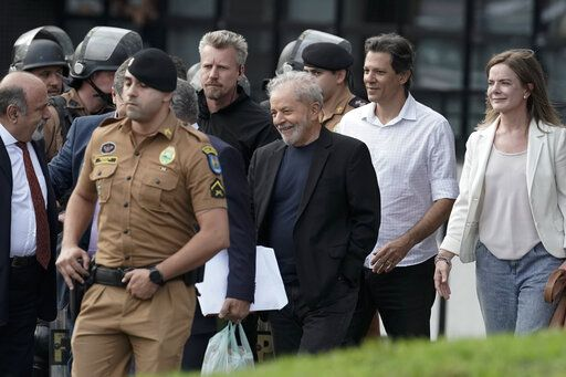 Brazil's former President Luiz Inacio Lula da Silva, center, smiles as he exits the the Federal Police headquarters where he was imprisoned on corruption charges in Curitiba, Brazil, Friday, Nov. 8, 2019. Da Silva walked out of a Curitiba prison Friday, less than a day after the Supreme Court ruled that a person can be imprisoned only after all the appeals have been exhausted. At right is President of the Workers' Party Gleisi Hoffmann.
