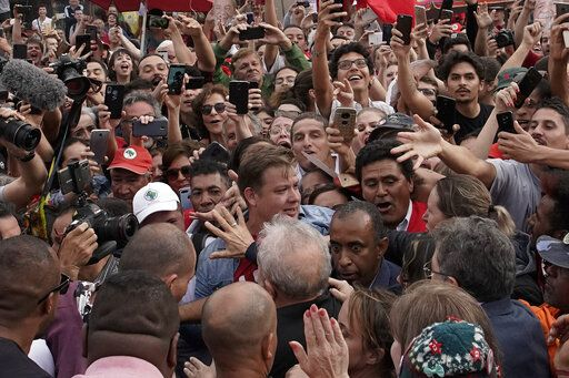 Brazil's former President Luiz Inacio Lula da Silva, bottom, back to camera, waves to supporters as he exits the the Federal Police headquarters where he was imprisoned on corruption charges in Curitiba, Brazil, Friday, Nov. 8, 2019. Da Silva walked out of a Curitiba prison Friday, less than a day after the Supreme Court ruled that a person can be imprisoned only after all the appeals have been exhausted.
