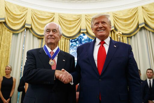 FILE - In this Oct. 24, 2019, file photo, President Donald Trump shakes hands with auto racing great Roger Penske during a Presidential Medal of Freedom ceremony in the Oval Office of the White House. Penske this week celebrated the crowning achievement of a career so rich in America's fabric that he last month received the Presidential Medal of Freedom by buying iconic Indianapolis Motor Speedway. On Sunday he will watch two of his drivers try to make NASCAR's championship race.