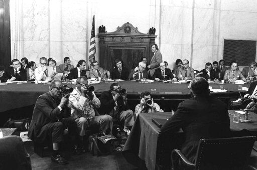 "FILE - In this Aug. 3, 1973, file photo, the Senate Watergate Committee hearings continueon Capitol Hill in Washington.. From left are: Sen. Lowell P. Weicker, Jr; Sen. Edward J. Gurney, Fred Thompson, Sen. Howard H. Baker, Jr; Rufus Edmisten, Sen. Sam Ervin; Sam Dash, Sen. Joseph M. Montoya, Sen. Daniel K. Inouye was absent. Testifying is Lt. Gen. Vernon Walters. In 1973, millions of Americans tuned in to what Variety called ""the hottest daytime soap opera"" _ the Senate Watergate hearings that eventually led to President Richard Nixon's resignation. For multiple reasons, notably a transformed media landscape, there's unlikely to be a similar communal experience when the House impeachment inquiry targeting Donald Trump goes on national television starting Wednesday"