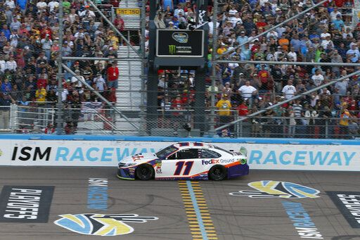Denny Hamlin (11) takes the checkered flag to win the NASCAR Cup Series auto race Sunday, Nov. 10, 2019, in Avondale, Ariz.
