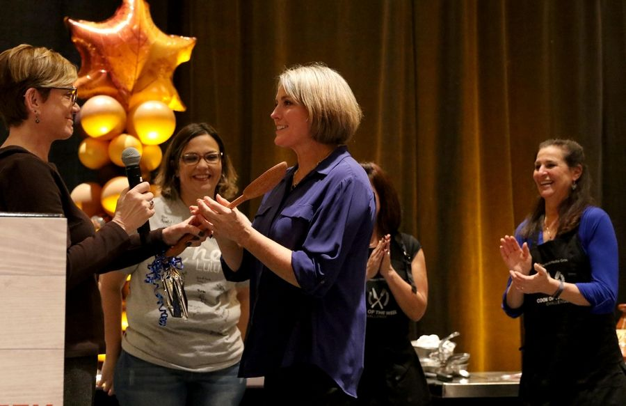 Leslie Meredith of Arlington Heights accepts the wooden spoon trophy from Eileen Brown of the Daily Herald at the Cook of the Week Challenge Finale at the Westin in Itasca on Monday evening.