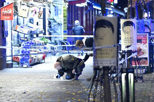 In this photo taken late Saturday, Nov. 9, 2019, a policeman works near the scene of a shooting, in Malmo, Sweden.  A 15-year-old boy was killed and another teenager was in critical condition after a shooting in a busy square in the southern city of Malmo, Swedish police said Sunday. Similar incidents and explosions in Malmo recently have alarmed politicians and residents. (Johan Nilsson/TT News Agency via AP)
