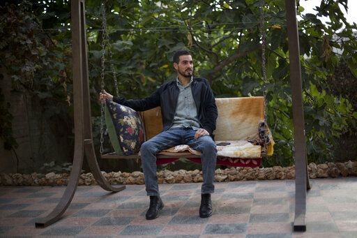 Palestinian Karam Qawasmi, who was shot in the back by Israeli forces in an incident caught on video last year, sits in his garden, in the West Bank city of Hebron, Sunday, Nov. 10, 2019. In his first interview since the video emerged last week, Karam Qawasmi said he was run over by a military jeep, then beaten for several hours before troops released him, only to shoot him in the back with a painful sponge-tipped bullet as he walked away.