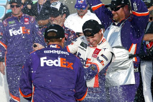 Denny Hamlin, center, gets sprayed with champagne by pit crew members in Victory Lane after he won the NASCAR Cup Series auto race Sunday, Nov. 10, 2019, in Avondale, Ariz.