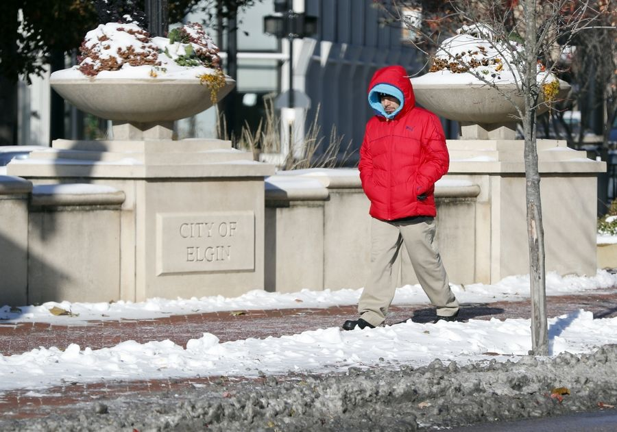 An unidentified man tries to stay warm as he walks in downtown Elgin Tuesday as temperatures dropped to record lows.