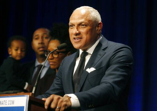 FILE - In this Nov. 27, 2018 file photo, Mississippi Democrat Mike Espy stands with family members as he talks to supporters in a crowded auditorium at the Mississippi Civil Rights Museum in Jackson, Miss., after losing the runoff election. On Tuesday, Nov. 12, 2019, Espy announced another run for U.S. Senate, setting up a 2020 rematch with Republican Cindy Hyde-Smith.