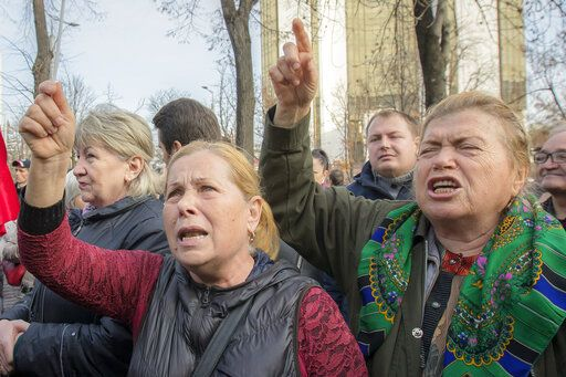 Supporters of the government shout slogans outside Moldova's parliament during a rally in Chisinau, Moldova, Tuesday, Nov. 12, 2019. Prime Minister Maia Sandu's government coalition between a pro-European group and a Russian-backed party has fallen after losing a no-confidence vote in parliament as 63 of 101 lawmakers supported the no-confidence motion.