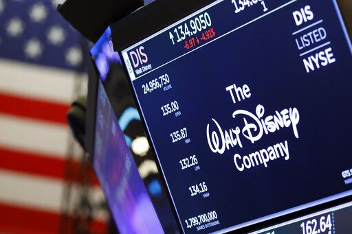 FILE - In this Aug. 7, 2019, file photo the logo for The Walt Disney Company appears above a trading post on the floor of the New York Stock Exchange. On Tuesday, Nov. 12, Disney Plus launches its streaming service.