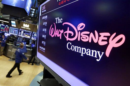 FILE - In this Aug. 8, 2017, file photo, The Walt Disney Co. logo appears on a screen above the floor of the New York Stock Exchange. On Tuesday, Nov. 12, Disney Plus launches its streaming service.