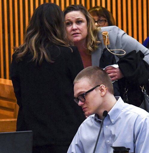 Tiffney Osborne, top, mother of Jesse Osborne, stands near him at the end of a special hearing before a judge, who will decide the 17-year-old's sentence, Tuesday, Nov. 12, 2019, in Anderson, S.C. Osborne pleaded guilty last year to two counts of murder for killing the boy at Townville Elementary School and shooting his father three times in the head so he could steal a pickup truck to get to his old school in September 2016. (Ken Ruinard/The Independent-Mail via AP)