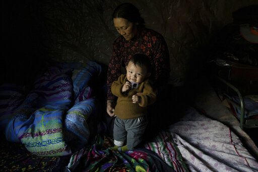 A Tibetan woman attends to a child in Angsai, an area inside the Sanjiangyuan region in western China's Qinghai province on Sunday, Aug. 25, 2019. A key question looms over the country's national parks project: Can China marry the goals of conservation and tourism, while safeguarding the livelihoods and culture of the approximately 128,000 people who live within or near the park's boundaries, many of them Tibetan?