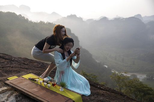 Women work on a photo for their tea products on a mountain top in Wuyishan in eastern China's Fujian province on Wednesday, Aug. 14, 2019. Zhu Chunquan, the China representative of the International Union for the Conservation of Nature, a Switzerland-based scientific group, notes that the country's economy has boomed over the past 40 years. But priorities are now expanding to include conserving the country's key natural resources. 'œIt's quite urgent, as soon as possible to identify the places, the ecosystems and other natural features'� to protect, Zhu says.