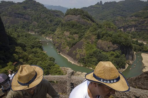 Visitors climb Tianyou peak in Wuyishan in eastern China's Fujian province on Wednesday, Aug. 14, 2019. The ambition to create a unified park system represents 'œa new and serious effort to safeguard China's biodiversity and natural heritage,'� says Duke University ecologist Stuart Pimm.