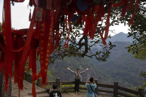 A visitor poses for a photo on Tianyou peak in Wuyishan in eastern China's Fujian province on Wednesday, Aug. 14, 2019.