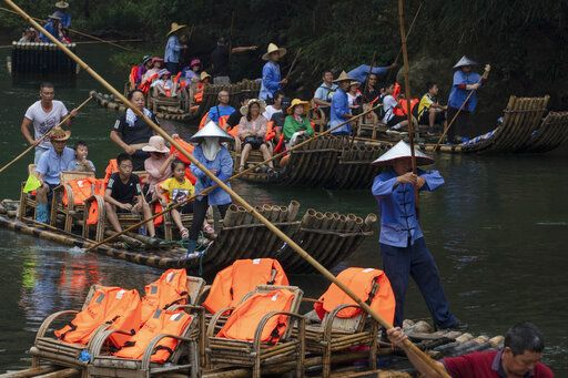 Tourists ride in bamboo rafts during a tour of the Nine Bends River in Wuyishan in eastern China's Fujian province on Thursday, Aug. 15, 2019. In August 2019, policymakers and scientists from China, the United States and other countries met in China to discuss the country's plans to create a unified park system with clear standards for limiting development and protecting ecosystems.