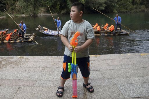A boy holds a water rifle on the banks of the Nine Bends River as bamboo raft operators wait for tourists in Wuyishan in eastern China's Fujian province on Thursday, Aug. 15, 2019. Zhu Chunquan, the China representative of the International Union for the Conservation of Nature, a Switzerland-based scientific group, notes that the country's economy has boomed over the past 40 years. But priorities are now expanding to include conserving the country's key natural resources. 'œIt's quite urgent, as soon as possible to identify the places, the ecosystems and other natural features'� to protect, Zhu says.