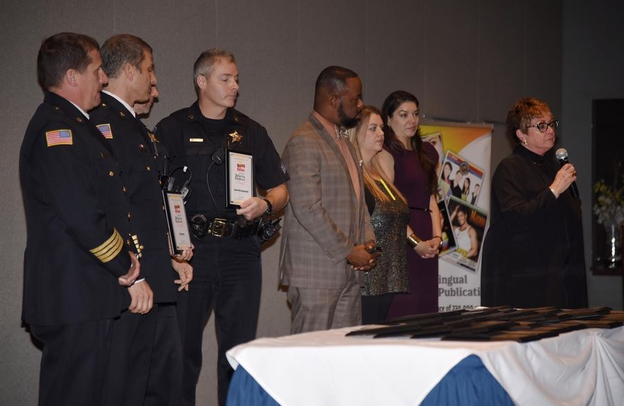 Reflejos manager of sales and operations Linda Siete, with microphone, introduces Aurora police officers and firefighters Wednesday during the 8th Annual Reflejos Reflecting Excellence Awards.