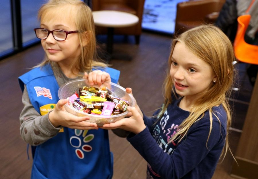 Troop members Charlie Gross, 7, right, and Cara McGuffin, 6, left, offer candy to Dunkin customers on Wednesday. Scouts from Elgin-based Troop No. 2341 bought coffee and other drinks for Dunkin customers as part of World Kindness Day Wednesday afternoon.