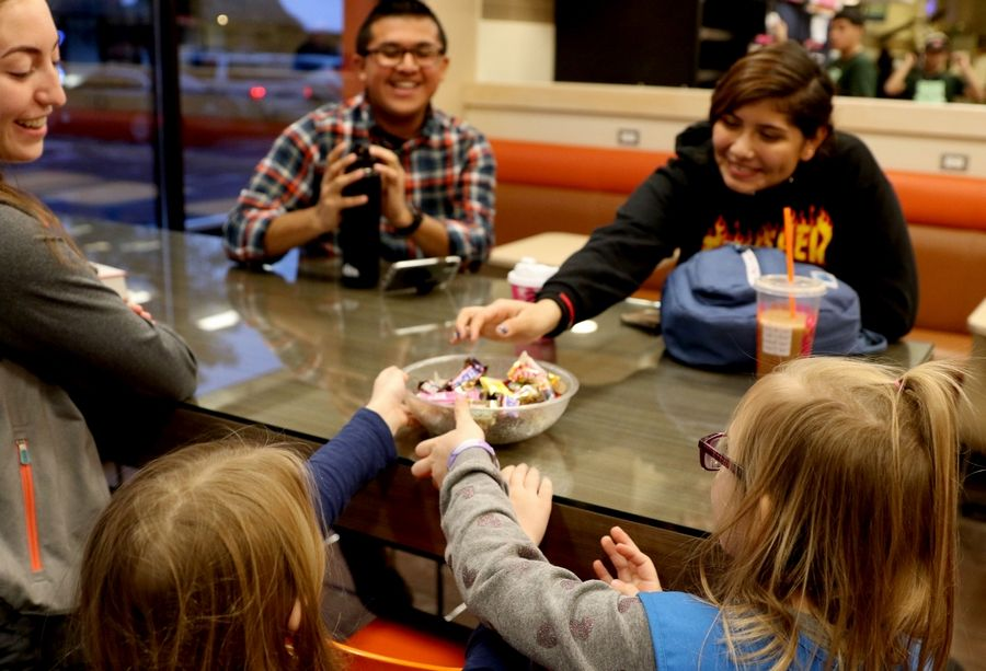 From left, Kaitlin Liebling of West Chicago, Brian De La Cruz of Wheaton and Yaretsi Selvas of Elgin smile as troop members Charlie Gross, 7, and Cara McGuffin, 6, offer candy. Scouts from Elgin-based Troop No. 2341 bought coffee and other drinks for Dunkin customers in Elgin as part of World Kindness Day Wednesday afternoon.