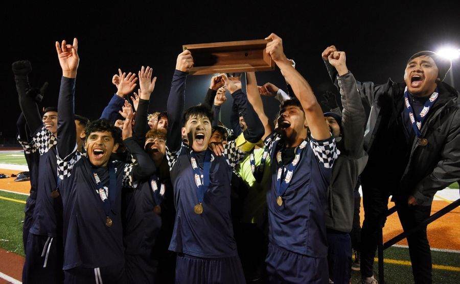 The West Chicago Wildcats hold up their trophy for the fans after defeating Morton in the Class 3A state soccer championship in Hoffman Estates Saturday.
