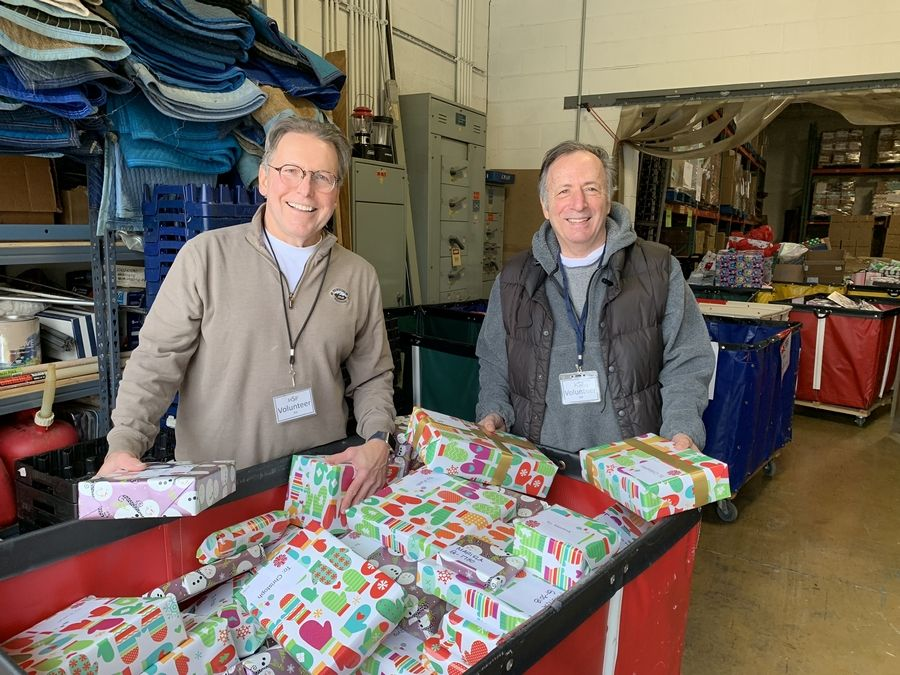 "Humanitarian Service Project volunteers Denny Deslavriers, left, and Mike Bolsoni look over the gifts to be distributed to local, low-income children as part of the charity's annual ""Christmas Offering"" program."