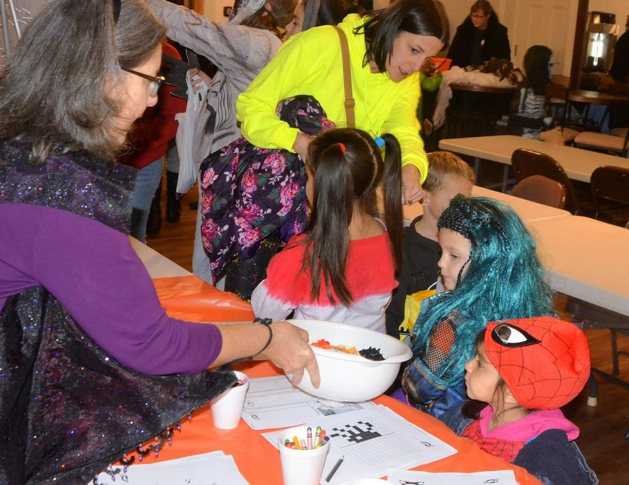 A volunteer offers treats to trick-or-treaters during a Halloween party at Wesley United Methodist Church in Aurora. The party, which replaced an outdoor trunk-or-treat event, featured a hot dog dinner, tabletop trick-or-treating stations and games.