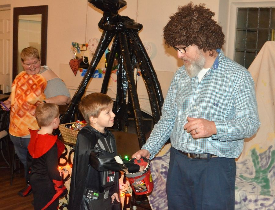 The Rev. John Bell, right, pastor at Aurora's Wesley United Methodist Church, greets trick-or-treaters at a church Halloween party. Left is Marea Clement, volunteer from Aurora University Dunham STEM school.