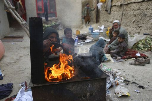 In this Oct. 29, 2019 photo, Yousuf, who fled with his family from his home in eastern Afghanistan eight years ago to escape the war, sits with children while his wife burns plastic as she makes tea, in Kabul, Afghanistan. In the capital, Kabul, five of his children died, not from violence or bombings, but from air pollution, worsened by bitter cold and poverty.