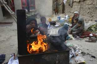 In this Oct. 29, 2019 photo, Yousuf, who fled with his family from his home in eastern Afghanistan eight years ago to escape the war, sits with children while his wife burns plastic as she makes tea, in Kabul, Afghanistan. In the capital, Kabul, five of his children died, not from violence or bombings, but from air pollution, worsened by bitter cold and poverty. (AP Photo/Rahmat Gul)