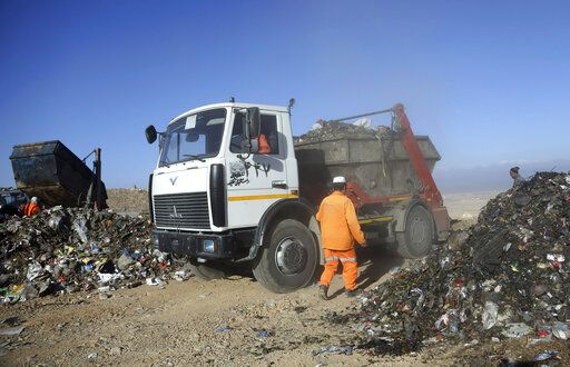 In this Oct. 23, 2019 photo, trucks unload garbage at the Kabul Municipality dump yard, on the outskirts of Kabul, Afghanistan. Authorities are trying to tackle pollution in the country's capital, which may be even deadlier than 18-year-old war. Most days a layer of smog covers Kabul, and it gets worse in the winter, when people burn coal, garbage, plastic and rubber to heat their homes.