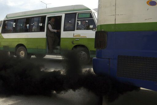 In this Oct. 16, 2019 photo, smoke comes out from the exhaust pipe of an old mini-bus in Kabul, Afghanistan. Authorities are trying to tackle pollution in the country's capital, which may be even deadlier than 18-year-old war. Most days a layer of smog covers Kabul, and it gets worse in the winter, when people burn coal, garbage, plastic and rubber to heat their homes.