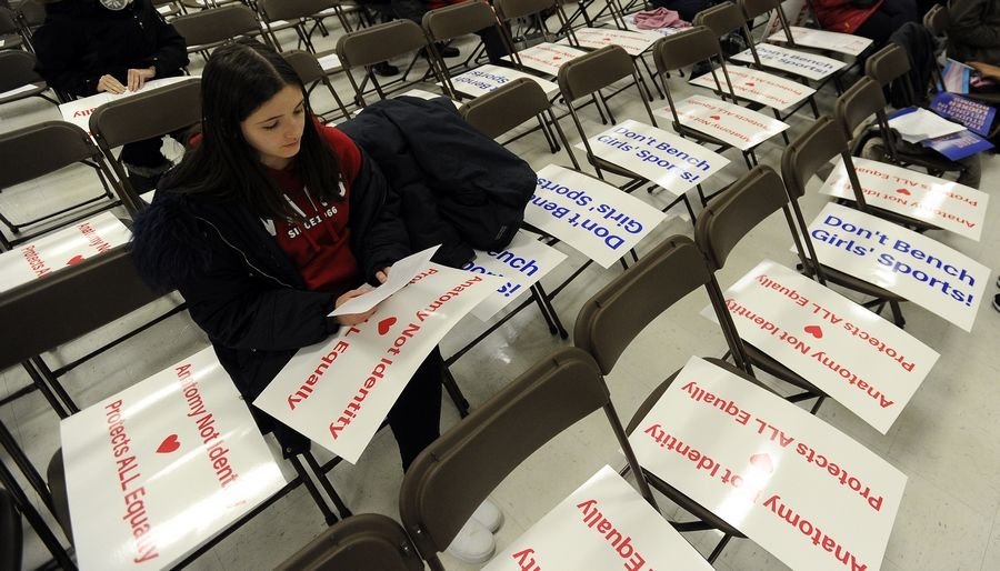 Sarah Harrington of Hoffman Estates, who goes to a private school, sits among signs against allowing transgender students full access to locker rooms in District 211. The school board, which met Thursday night at Fremd High School in Palatine, granted access.